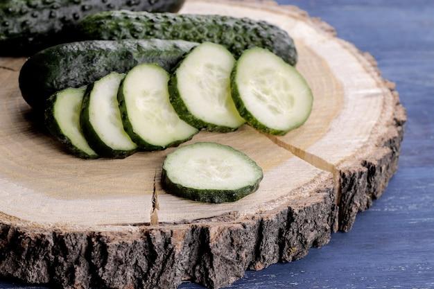 Concombres frais. concombre tranché sur un support en bois sur une table en bois bleue