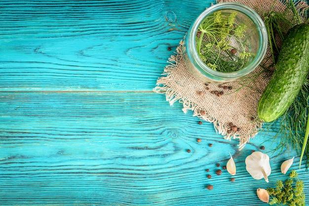 Concombres frais prêts pour la mise en conserve avec de l'aneth, de l'ail et des épices sur bois bleu