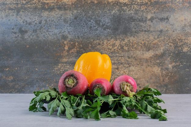 Concombres frais, radis rouges et poivre sur table en pierre. photo de haute qualité