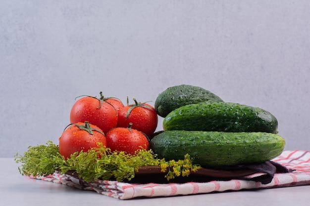 Concombres frais, tomates et basilic sur nappe.