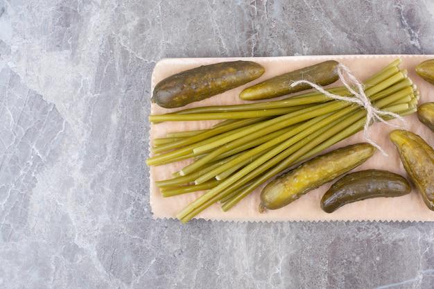 Concombres et haricots verts fermentés sur planche de bois