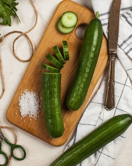 Concombres longs et lisses entiers et coupés en anneaux sur une planche en bois avec du gros sel et un couteau à côté d'eux
