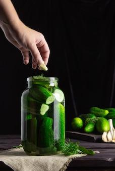 Concombres à mariner. concombres dans un bocal, la main met les ingrédients. vintage, fond sombre.