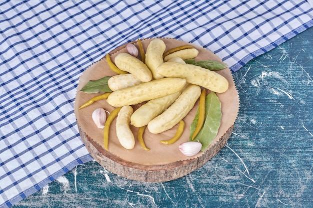 Concombres marinés, ail, poivrons et feuille sur plaque en bois avec nappe.
