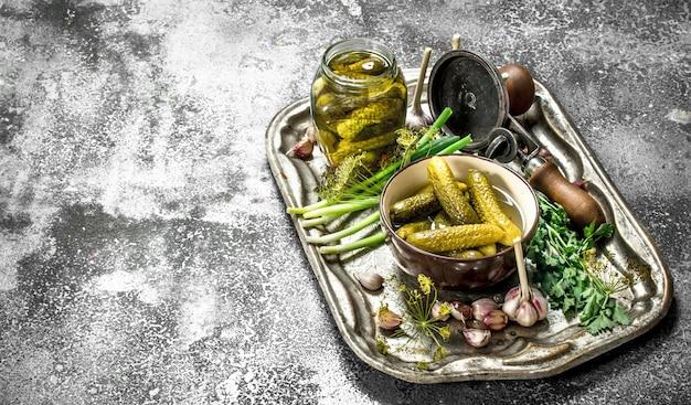 Concombres marinés aux herbes et épices sur un plateau en acier sur une table rustique.