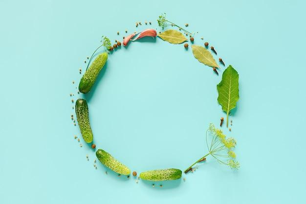 Concombres marinés. cadre de cercle avec espace de copie des ingrédients pour les cornichons marinés sur fond bleu.