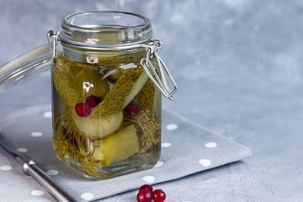 Concombres marinés dans un bocal en verre et sur une planche de bois. aliments fermentés sur fond gris. copiez l'espace.