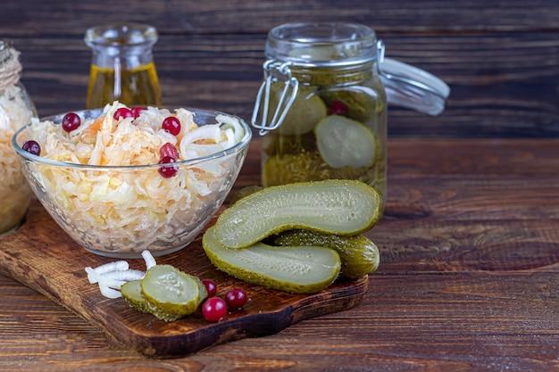 Concombres marinés dans un bocal en verre sur une planche en bois et choucroute aux canneberges. aliments fermentés. copiez l'espace.