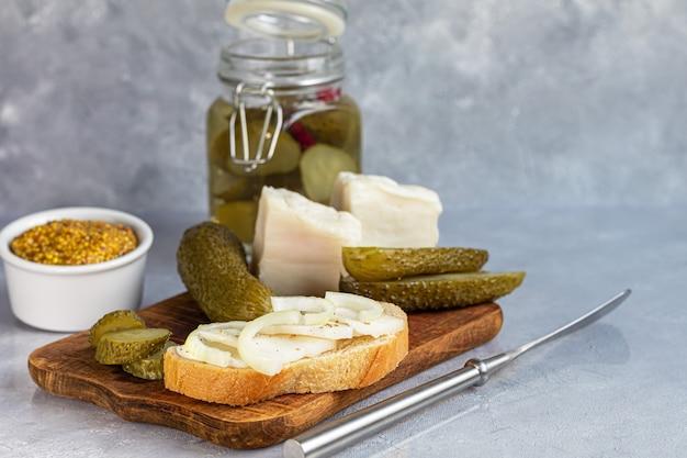 Concombres marinés dans un bocal en verre sur une planche de bois et un sandwich au bacon. haricots de moutarde en arrière-plan. aliments fermentés. copiez l'espace.