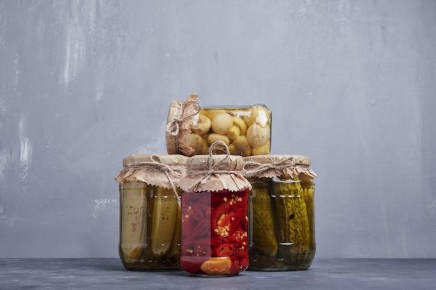 Concombres marinés, olives et poivrons rouges dans des bocaux en verre sur fond bleu.