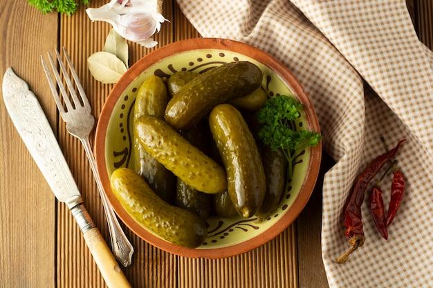 Concombres marinés. pickles de légumes dans un bol, table en bois.