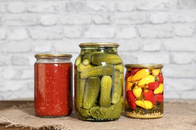 Concombres marinés tomates italiennes dans leur propre jus et mini piments dans des bocaux en verre