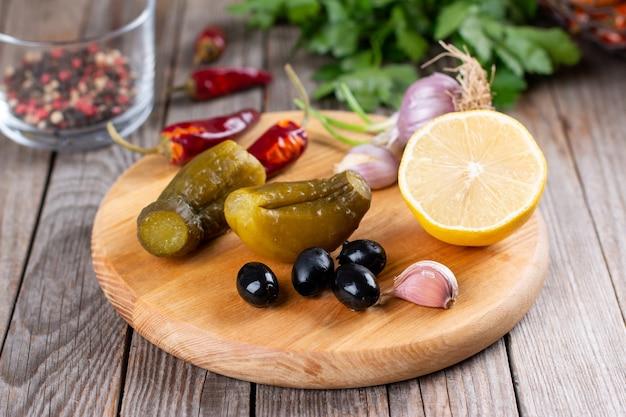 Concombres, olives, ail sur une planche de bois. cornichons pour cuisiner des plats salés