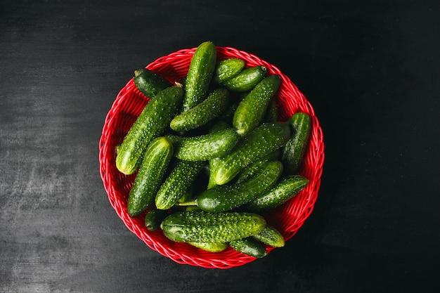Concombres organiques fraîches dans un panier rouge sur une table en bois blanche avec poivrons verts et rouges, piment, fenouil, sel, poivre noir, ail, pois, gros plan, concept santé, vue de dessus, pose à plat