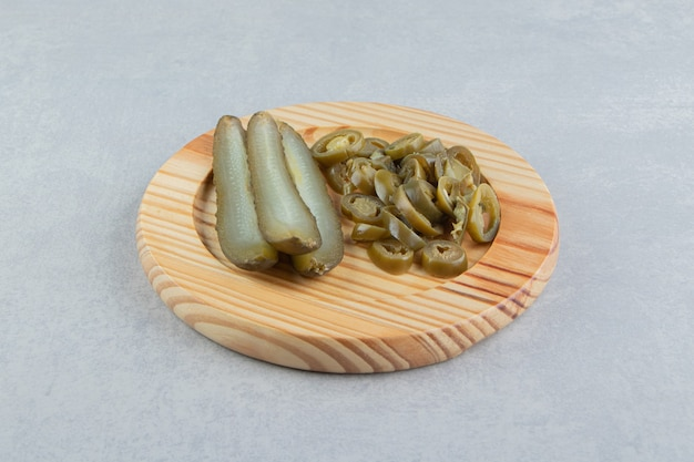 Concombres et poivrons marinés sur plaque de bois.
