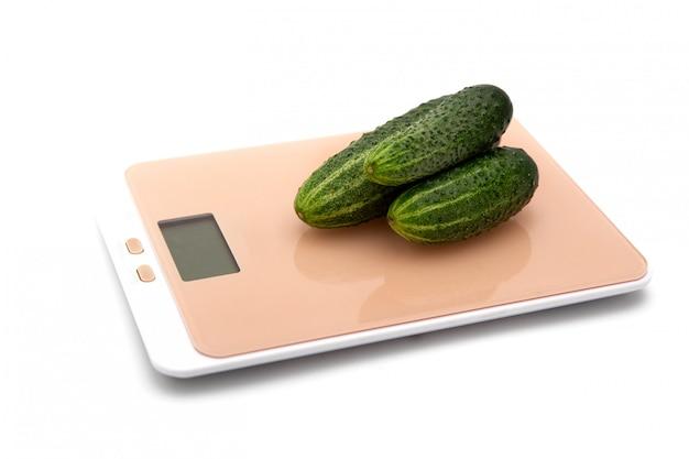 Concombres verts sur une balance de cuisine sur blanc. le concept de pesée.