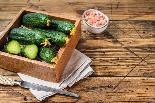 Concombres verts frais dans une boîte en bois. fond en bois. vue de dessus. espace de copie.