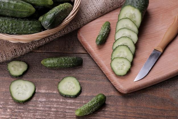 Concombres verts frais dans un panier et tranches de concombres sur une table en bois marron. les légume