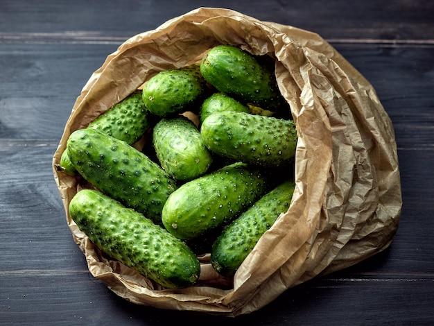 Concombres verts frais dans un sac en papier sur une table de cuisine en bois foncé