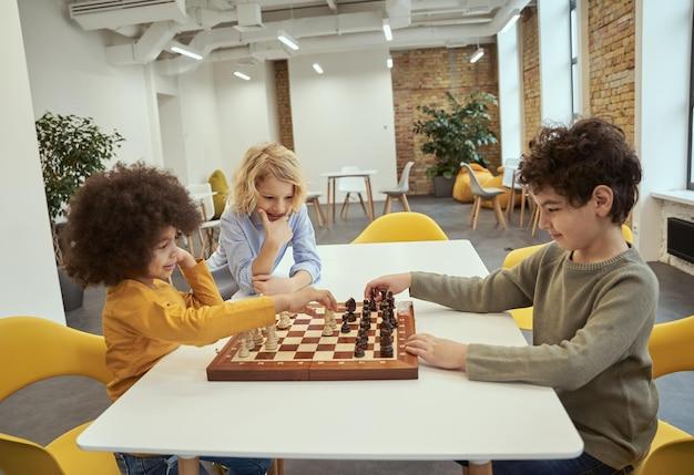 Concours joyeux petits garçons divers assis à la table et jouant aux échecs à l'école