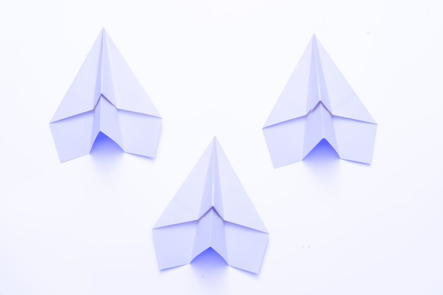 Concurrence commerciale. trois avions en papier bleu ciel isolated on white