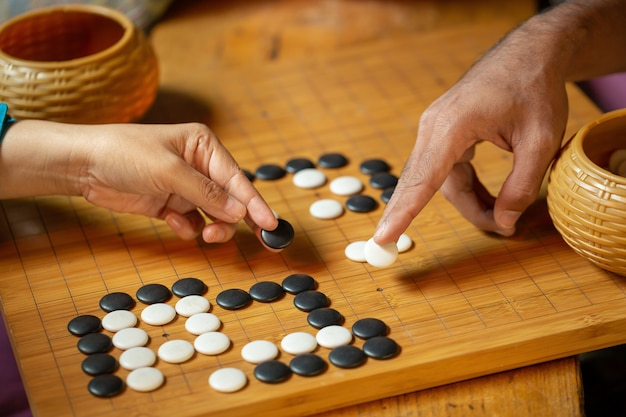Un concurrent place une pièce de marbre sur un jeu de plateau go.