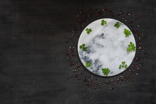 Condiments et épices sur panneau de pierre rond.