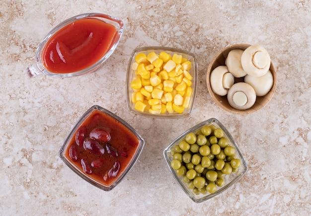Condiments et portions de légumes dans des bols