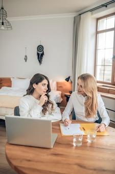 Conditions de l'accord. deux femmes assises à la table et discutant des termes d'un accord