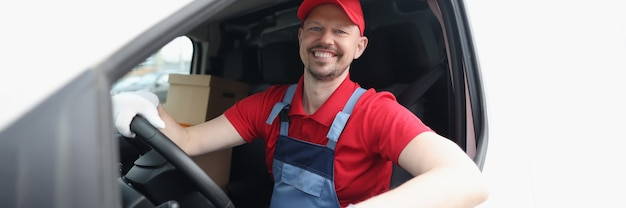Conducteur de courrier masculin souriant au volant d'une voiture agrandi