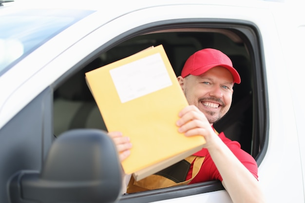 Le conducteur de courrier masculin souriant tient le courrier dans ses mains