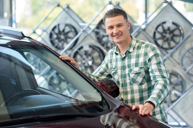 Conducteur élégant attrayant, main dans la main à l'avant du véhicule.