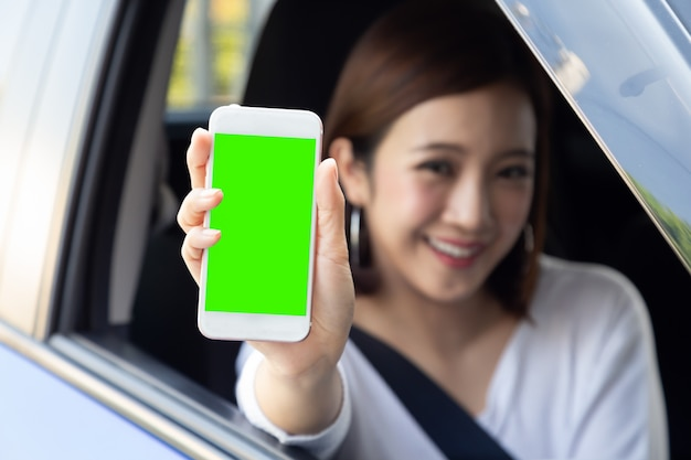 Conducteur de femme asiatique assis dans la voiture et tenant un téléphone mobile avec écran vert