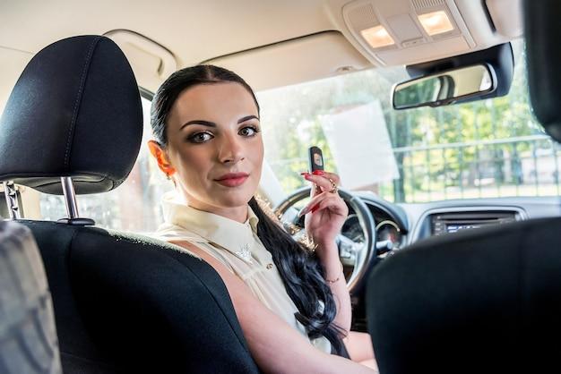 Conducteur de femme montrant la clé de voiture à l'intérieur de l'automobile