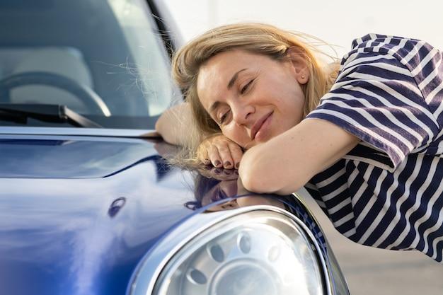 Conducteur de femme moyenne embrassant le capot de la voiture après avoir détaillé la publicité d'assurance automobile de polissage