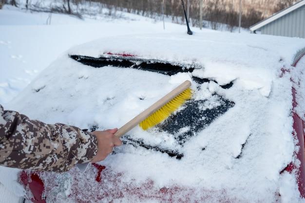 Conducteur à la main à l'aide d'une brosse balayant la neige sur le pare-brise de la voiture en hiver orageux