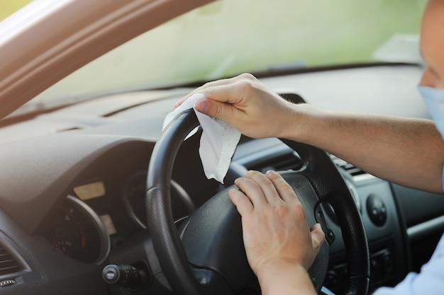 Le conducteur nettoie le volant de sa voiture avec un chiffon antibactérien. concept antiseptique, hygiène et soins de santé. mise au point sélective