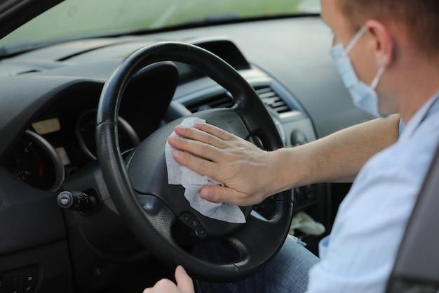 Le conducteur nettoie le volant de sa voiture avec un chiffon antibactérien.