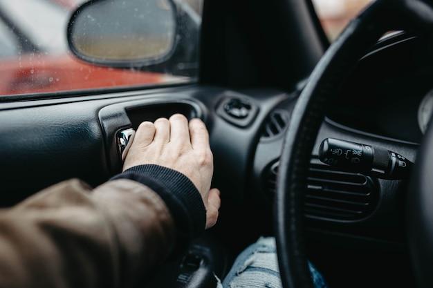 Le conducteur ouvre la porte de la voiture de l'intérieur