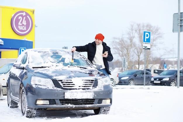 Un conducteur se tient devant une voiture. le propriétaire nettoie la voiture de la neige en hiver. voiture après une chute de neige.
