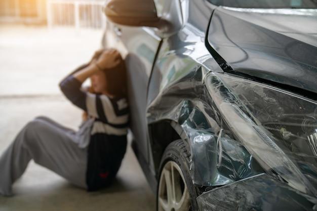 Conducteur stressé assis en bord de route après un accident de la circulation