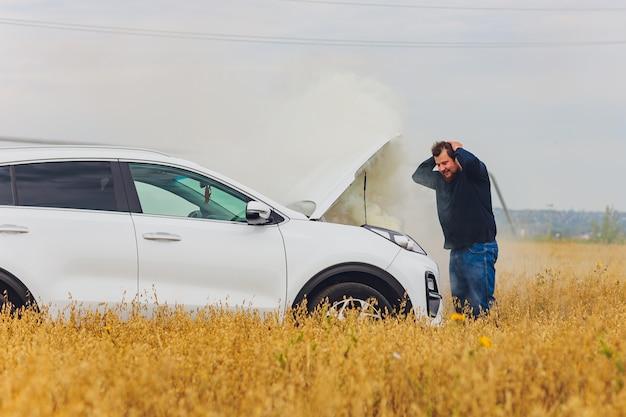 Conducteur stressé et frustré tirant ses cheveux tout en se tenant sur la route à côté d'une voiture cassée. problèmes de road trip et concepts d'assistance. fumée.