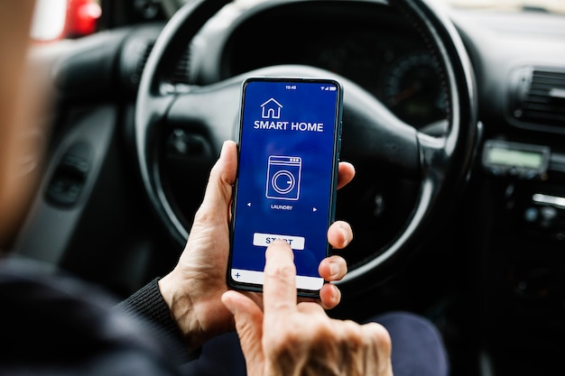 Conducteur utilisant l'application smart home sur smartphone dans le concept iot de l'internet des objets en voiture