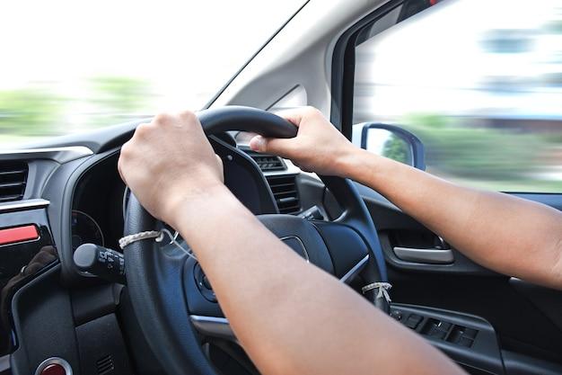 Conducteur de voiture mains sur le volant conduisant une voiture avec arrière-plan flou de mouvement.