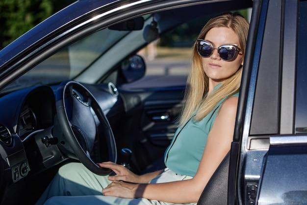 Une conductrice aux cheveux blonds dans des lunettes de soleil est assise sur le siège de la voiture pendant la journée.