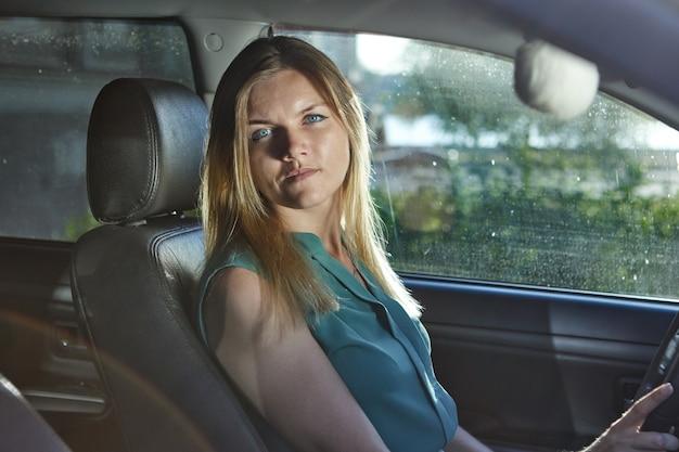 Une conductrice aux cheveux blonds est assise sur le siège de l'automobile pendant la conduite.