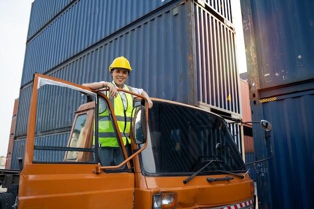 Une conductrice de camion asiatique porte un casque jaune et un gilet de sécurité devant les camions.