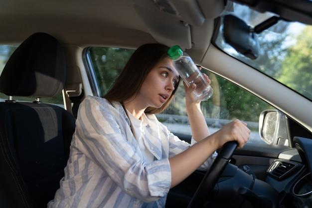 Une conductrice épuisée souffrant de maux de tête par temps chaud applique une bouteille d'eau sur le front