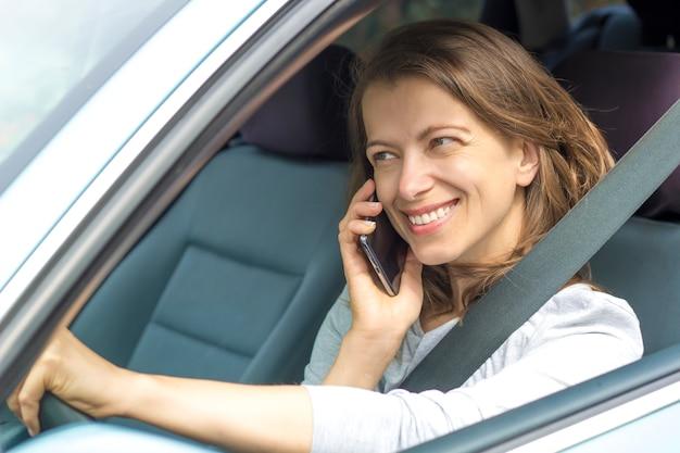 Une conductrice parle au téléphone en étant assise dans la voiture.