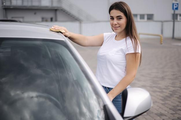 Une conductrice séduisante et joyeuse essuie le pare-brise de sa voiture à l'aide d'un chiffon dans un lave-auto en libre-service